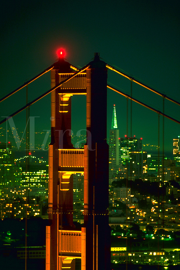 View of the San Francisco city skyline at night through on of the Golden Gate Bridge towers.<br />