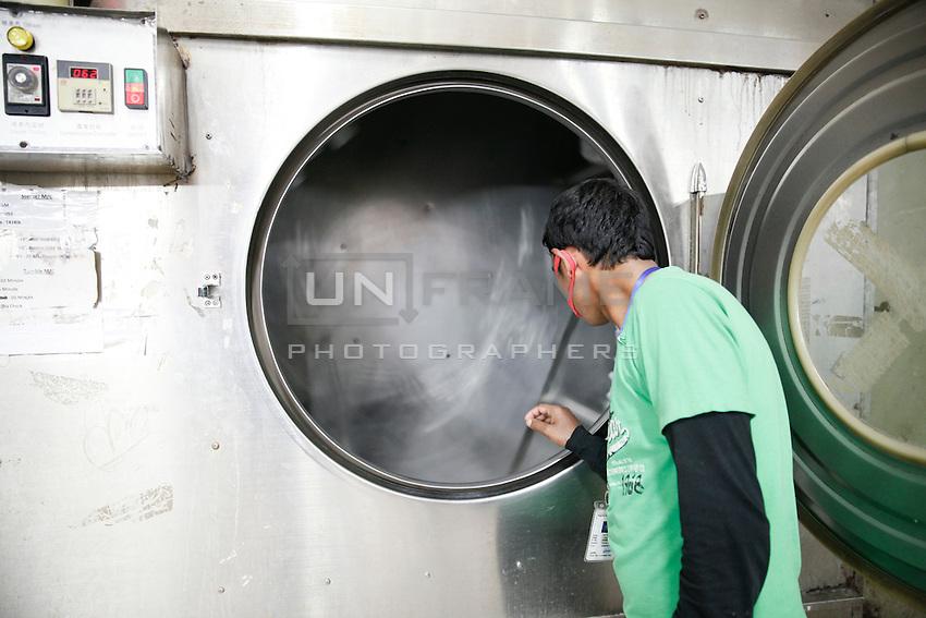 A worker looks inside of a washing machine in a garments factory. Gazipur, near Dhaka, Bangladesh
