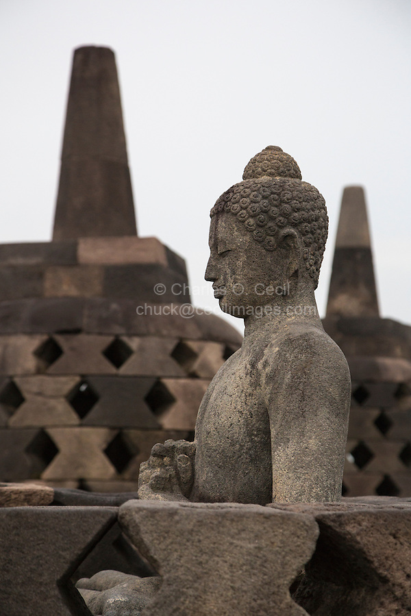 Borobudur, Java, Indonesia.  Buddha Statue, Upper Terrace.  The diamond-shaped holes symbolize the passions that still linger as men rise toward Nirvana.  On the next higher terrace the holes in the stupas are square, symbolizing  the overcoming of passions as one approaches Nirvana.