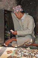 Kathmandu, Nepal.  Money-Changer in Market, Durbar Square, wearing a Topi, Traditional Nepali Hat.