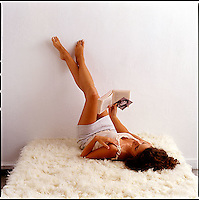 Woman with legs up on wall reading a book and looking at a boy's photo<br />