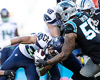 CHARLOTTE, NC - DECEMBER 15: Travis Homer #25 of the Seattle Seahawks is tackled by Bruce Irvin #55 of the Carolina Panthers during a game between Seattle Seahawks and Carolina Panthers at Bank of America Stadium on December 15, 2019 in Charlotte, North Carolina.