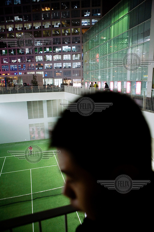 A tennis court is nestled between highrise buildings in a fashionable area of the Central Business District.