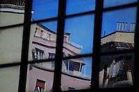 Rome, via Morgagni. A reflected image captured between the mirror glass walls of a group of modern buildings, that are surrounded by old ones, in via Morgagni. There is, in particular, a distorted terrace angle and a series of smokestacks.
