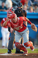 Williamsport Crosscutters catcher Logan Moore #10 gets in position to back up first base as umpire Jacob Dallas looks on during a NY-Penn League game against the Batavia Muckdogs at Dwyer Stadium on August 24, 2012 in Batavia, New York.  Williamsport defeated Batavia 7-4.  (Mike Janes/Four Seam Images)