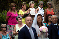 Tourist onlookers watch as a bride, center, prepares to march into Convento di San Francesco for her wedding on Saturday, Sept. 19, 2015, in Sorrento, Italy. (Photo by James Brosher)