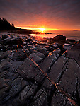 The sun rises over an unnamed beach at low tide in Acadia National Park, Maine, USA
