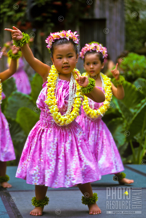 Young hula dancers wearing yellow plumeria leis, Lei Day celebration at Hilton Hawaiian Village Hotel