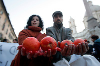 Manifestanti mostrano arance colorate con vernice rossa simbolizzante il sangue, durante una protesta in piazza Navona, Roma, 12 gennaio 2010, in concomitanza con l'audizione al Senato del Ministro dell'Interno Roberto Maroni sugli scontri tra immigrati e polizia a Rosarno, in Calabria, in seguito agli episodi di violenza nei confronti di alcuni lavoratori extracomunitari impegnati in agricoltura..Demonstrators hold oranges painted in red to symbolize blood during a protest in Rome's Piazza Navona in solidarity with African farmworkers resident in Rosarno, southern Italy, protesting against racist attacks. .UPDATE IMAGES PRESS/Riccardo De Luca