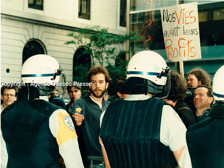 May 1998 File Photo - Montreal (qc) CANADA -  A peacefull demonstrator offer flower to policemen protecting the site of the Conference de Montreal<br /> <br /> PHOTO :  Agence Quebec Presse