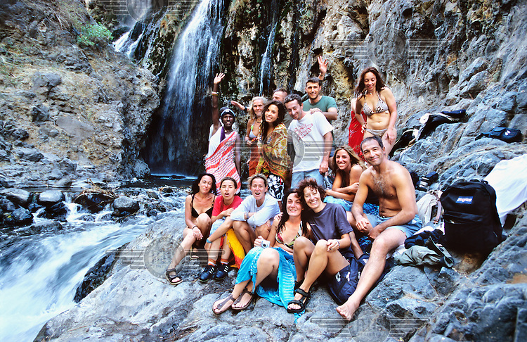 Italian tourists enjoying a bath in a cold waterfall near Lake Natron in the Crater Highlands region, along the East African rift in Tanzania.