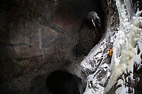 Ice climber in yellow jacket climbs colourful underground ice structure, Sweden