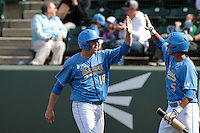 Cody Regis #18 of the UCLA Bruins is greeted by Kevin Williams #5 during a game against the Washington State Cougars at Jackie Robinson Stadium on March 24, 2012 in Los Angeles,California. UCLA defeated Washington 12-3.(Larry Goren/Four Seam Images)