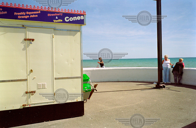 A closed ice cream stand by the sea.