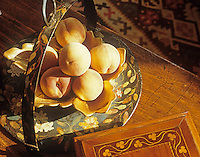 Peaches are displayed in a ceramic bowl set inside a painted metal dish,