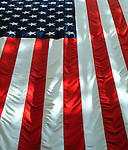 Vertically hung American flag with light and shadows.