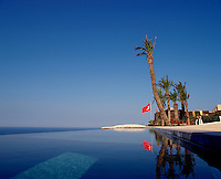 The deep blue of the clear sky is reflected in the infinity pool situated on one of the roof terraces