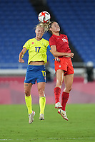 YOKOHAMA, JAPAN - AUGUST 6: Caroline Seger #17 of Sweden goes up for a header with Janine Beckie #16 of Canada during a game between Canada and Sweden at International Stadium Yokohama on August 6, 2021 in Yokohama, Japan.