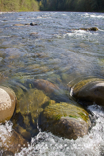 Water pours over round boulders.