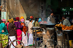 Poor Indian people lines up for a free meal at a shop donated by a temple in Varanasi, Uttar Pradesh, India.