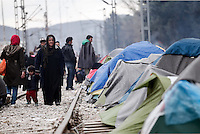 Pictured: Migrants walk on the railway track next to the camp  Monday 07 March 2016<br /> Re: Refugees at the Greek FYRO Macedonian border in Idomeni, Greece.