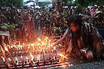 "A young woman at the annual Taong Putik, or ""mud people,"" festival, lights a votive candle on the steps of the Catholic church in Bibiclat, on Luzon island, Philippines. The festival honors St. John the Baptist, and devotees smear their bodies with mud and dress in cloaks made from banana leaves and vines, which symbolize the animal skins the saint wore in the Bible. June 24, 2011."