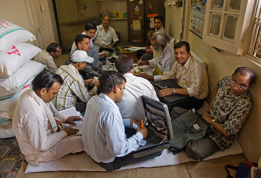 BUSINESS MEN with LAPTOP COMPUTERS sit on the floor in CHANDNI CHOWK - OLD DELHI, INDIA