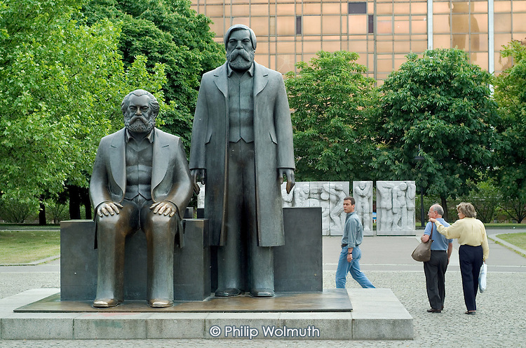 Tourists photograph statues of Karl Marx and Friedrich Engels in Berlins Marx-Engels Platz