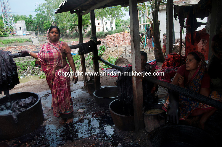 Shomarani Mondal (45)(left) at her tie and die Saree factory. She is a benificiary of Bandhan - one of the biggest micro credit company in India. She employed 15 people and makes a profit of 500 usd per month. Rajarlat village, Canning, West Bengal, India. Arindam Mukherjee