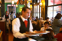 Waiters serving food and guests eating lunch, dry cured hams hanging from the ceiling,, in the restaurant El Palenque, the sword fish swordfish, in the Mercado del Puerto, the market in the port harbour harbor where many people go and eat and shop on weekends Montevideo, Uruguay, South America