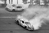 HAMPTON, GA - NOV 3:  Kyle Petty, #7 Ford, crashes as his father Richard Petty, #43 Pontiac races past during the Atlanta Journal 500 NASCAR Winston Cup race at Atlanta Motor Speedway, November 3, 1985. (Photo by Brian Cleary/www.bcpix.com)