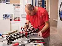 Trainee tiler using the tile cutter,  Able Skills training centre, Dartford, Kent.
