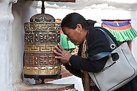 Bodhnath, Nepal.  Buddhist Worshiper Praying at Prayer Wheel.