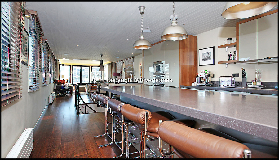 BNPS.co.uk (01202 558833)<br /> Pic: Riverhomes/BNPS<br /> <br /> Kitchen/bar.<br /> <br /> Heart of Lightness - Tardis like houseboat on the Thames.<br /> <br /> A houseboat that looks more like a luxurious penthouse suite inside has gone on the market for a whopping £1.5 million - because it's in one of London's most exclusive locations.<br /> <br /> The 100ft vessel was once a former Dutch barge taking supplies up and down the Thames until it was retired from service in the 1960s and left to rot.<br /> <br /> But a decade later it was salvaged and turned into a houseboat before undergoing a complete refurbishment four years ago and moved to a premier mooring alongside one the swankiest addresses in the city.<br /> <br /> The plush houseboat, berthed at the entrance to Cheyne Walk, now boasts a lavish living room, stylish 50ft-long kitchen, a spiral staircase, two opulent bedrooms, three bathrooms and even a sun terrace.<br /> <br /> And despite its eye-watering £1.5m asking price, experts at Riverhomes estate agents say the houseboat is actually a bargain and that anyone wanting to live in such luxury in the heart of Chelsea would have to shell out many millions more.