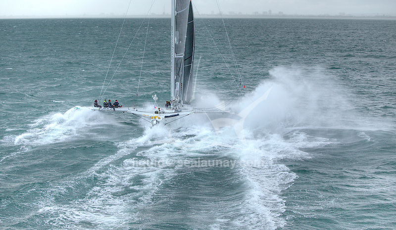 Aerial shoot of the Hydroptere sailing in the Solent, Cowes, Isle of Wight, United Kingdom..Now the fastest sailing boat in the world with an average speed of 51.36 knots over 500 meters and 50.17 knots over one nautical mile, the flying trimaran is currently heading to the open sea.
