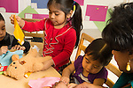 """Education preschool 3 year olds teacher with group of a boy and two girls """"dressing"""" stuffed teddy bears in costumes they fashioned"""