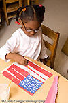 Preschool ages 3-5 art activity making US flags from cut paper strips gluing strips onto another sheet and painting stars vertical girl at work