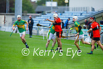 Ballyheigue's Jordan Goggin hand passes the ball out of danger as  Lixnaw's James Flaherty challenges him in Round 2 of the County Senior Hurling championship,