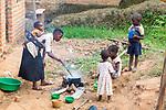 Children Watching As Mother Stirs Pot
