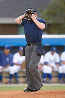 Home plate umpire Jonathan Bailey adjusts his mask at Burlington Athletic Park in Burlington, NC, Monday August 11, 2008. (Photo by Brian Westerholt / Four Seam Images)