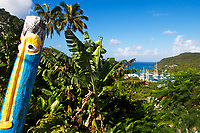 Lush Marigot Bay vegetation and boats on the turquoise sea, with a colorful wood sculpture, Saint Lucia (Sainte-Lucie), Caribbean Windward Islands