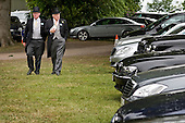 Two men in top hats in the car park at Ascot racecourse.