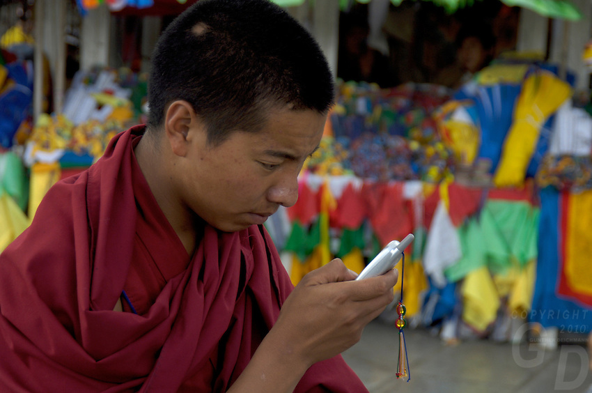 A Buddhist Monk and his simple Cell Phone. Street life and scenes in Lhasa, Tibet