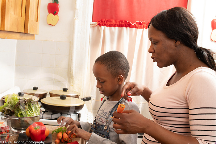 Mother in kitchen with 10 year old son, food preparation, getting ready to make salad