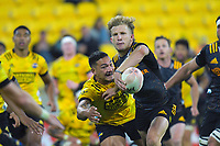 Damien McKenzie gets his pass away under pressure from Hurricanes' Billy Proctor during the Super Rugby Aotearoa match between the Hurricanes and Chiefs at Sky Stadium in Wellington, New Zealand on Saturday, 20 March 2020. Photo: Dave Lintott / lintottphoto.co.nz