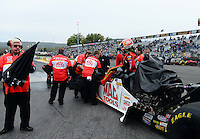 Oct. 7, 2012; Mohnton, PA, USA: NHRA crew Members for top fuel dragster driver Doug Kalitta cover the dragster as it starts raining again during qualifying for the Auto Plus Nationals at Maple Grove Raceway. Mandatory Credit: Mark J. Rebilas-