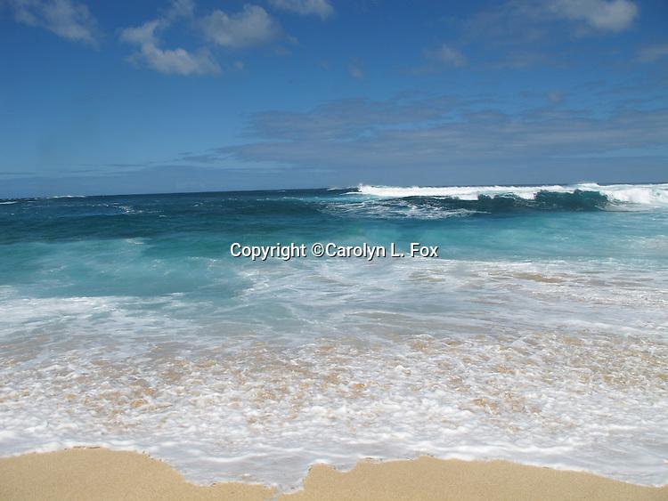 Waves rush up on the sands of Kauai, Hawaii.