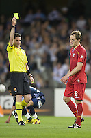 MELBOURNE, AUSTRALIA - OCTOBER 30: Adam Hughes of United is given a yellow card for his challenge on Marvin Angulo of the Victory during the round 12 A-League match between the Melbourne Victory and Adelaide United at Etihad Stadium on October 30, 2010 in Melbourne, Australia.  (Photo by Sydney Low / Asterisk Images)
