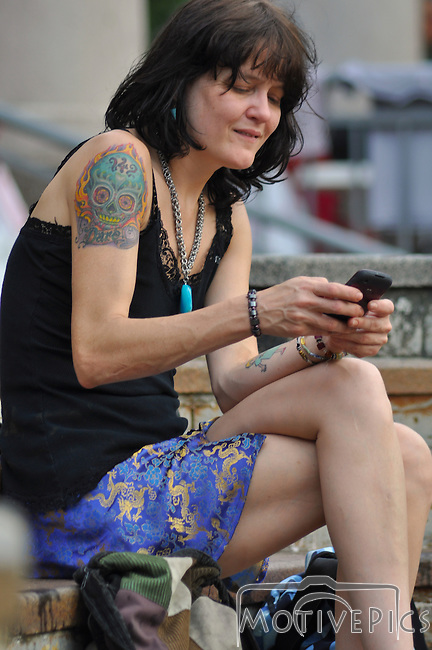 Jam for Joplin was a festival dedicated to relief for the tornado ravaged Joplin, MO.  Sunday, June 26th, 2011.  www.MotivePics.com<br /> Tattoo lady checking smart phone.