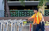 Local male airport employee maintaining luggage carts, Honolulu International Airport, O'ahu